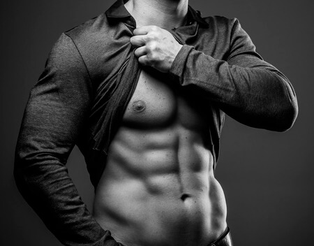 40107700 - muscular guy poses showing his abs and muscular body