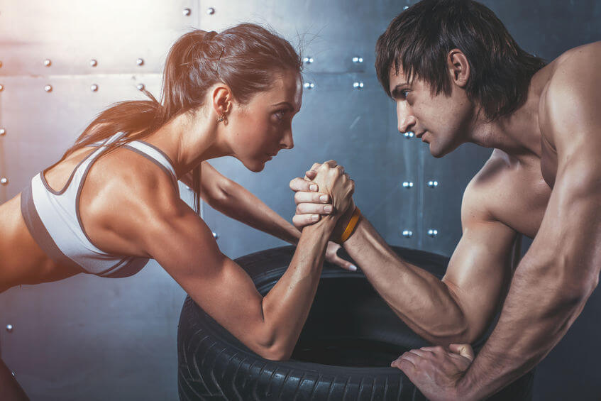 40321564 - athlete muscular sportsmen man and woman with hands clasped arm wrestling challenge between a young couple crossfit fitness sport training lifestyle bodybuilding concept