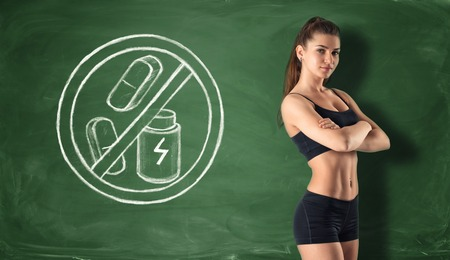 63066536 - cropped portrait of fitness girl on the background of a blackboard with a sign that prohibit dry protein and pills. healthy lifestyle. nutrients and vitamins. fitness and sport.