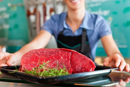 9860820 - working in a butcher's shop - shop assistant with meat