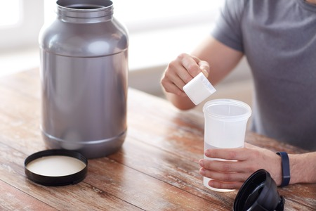 53578413 - sport, fitness, healthy lifestyle and people concept - close up of man in fitness bracelet with jar and bottle preparing protein shake