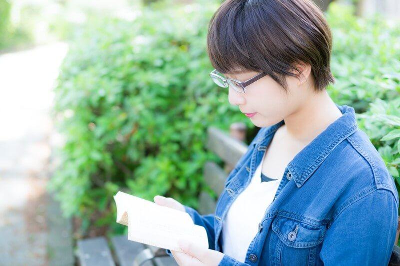 公園のベンチで読書をする文学少女